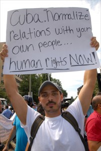 """A young man across the street from the Cuban Embassy in Washington calls for """"Human Rights Now!"""" on the island."""