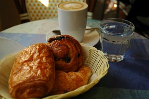 A basket of pastries and a caffe latte