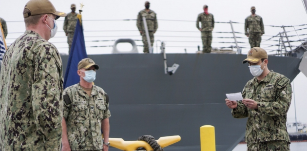 Cmdr. Jeremiah Petersen, right, reads his orders to assume command of USS Fort Worth (LCS 3) from Cmdr. Colin Corridan, left, during a change of command ceremony. Capt. Matthew McGonigle, commander of Littoral Ship Squadron ONE, center, presides over the change of command. (U.S. Navy photo by Lt. j.g. Sheryl Acuna)