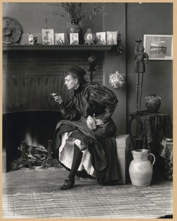 Women Behaving Badly: 400 Years of Power and Protest: Frances Benjamin Johnston.Frances Benjamin Johnston full-length portrait, seated in front of a fireplace, facing left, holding cigarette in one hand and a beer stein in the other, in her Washington DC studio. 1896.