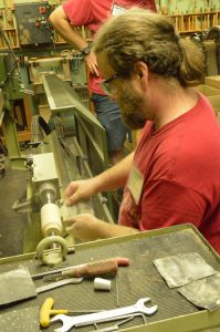 Mark Supik & Co. Woodturning - Matt Saindon giving a new tap handle a bit of finish sanding. (Anthony C. Hayes)