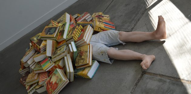 "One of th features pieces at the Babble exhibit in Baltimore is ""Benjamin"" a fake human figure half covered by books is the work of New York artists Alina and Jeff Bliumis. (credit Anthony C. Hayes)"