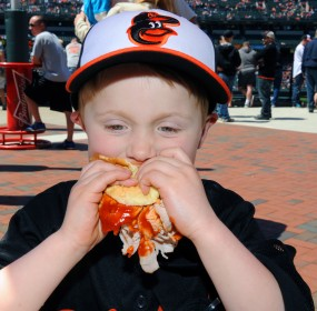 Baseball and Barbecue.  Young Luke Schwindt devours one of Boog's sandwiches at Camden Yards. (Jim Burger)