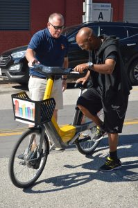 Jim Duffney gives veteran Onzea Robinson a quick demonstration of the Baltimore Bike Share pedelec bike. (Anthony C. Hayes)