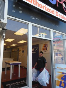 Hasim removes debris for his ransacked store. (Anthony C. Hayes)