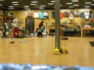 Employees clean up the pillaged DTLR shoe store on Monument Street. (Anthony C. Hayes)