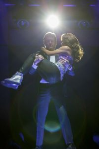 Bodyguard Frank Farmer (Judson Mills) carries singer Rachel Marron (Deborah Cox) to safety in The Bodyguard: The Musical.