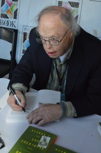 Robert Timberg signing a copy of his book Blue-Eyed Boy at the 2015 Baltimore Book Festival. (Anthony C. Hayes)