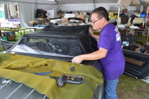 Eduardo Sousa of Al Knoch Interiors fits a new top on a silver Stingray. (Anthony C. Hayes)