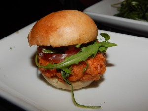 The Alaskan Salmon Cake Sliders have a hint of lemon and dill and are served with homemade tartar sauce, arugula, green onions and roma tomatoes. (Jon Gallo)