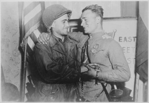 In an arranged photo commemorating the meeting of the Soviet and American armies, 2nd Lt. William Robertson (U.S. Army) and Lt. Alexander Silvashko (Red Army) stand facing one another with hands clasped and arms around each other's shoulders. In the background are two flags and a poster. (Wikipedia)