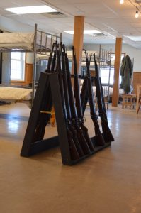 WWII-era rifles rest in a barrack gun rack at Ft. Indiantown Gap. The rifles are used by reenactors at the annual Battle of the Bulge event.(Anthony C. Hayes)