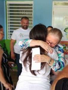 Angelique Sina of the Friends of Puerto Rico gets a hug from a grateful recipient of help.