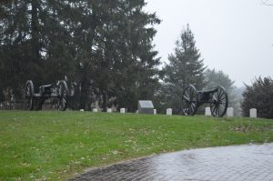 Flag burning: Canons stand as silent sentinals over some of the graves at Gettysburg National Cemetery. (credit Anthony C. Ha