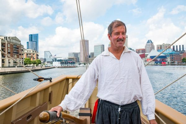 Captain Eric Speth at the helm of the history ship Godspeed. Godspeed is in Baltimore for the 2018 Maryland Fleet Week. (Michael Jordan / BPE)