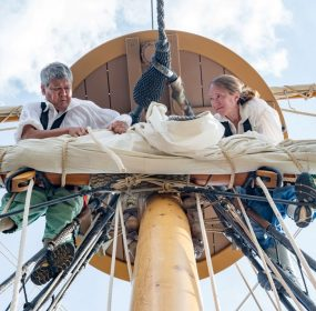 Crew members in early 17th century garb secure the main sail on the historic ship Godspeed. Godspeed is in Baltimore for the 2018 edition of Maryland Fleet Week. (Michael Jordan / BPE)