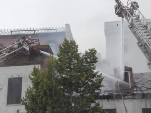 Firemen work to dampen a blaze in a building adjacent to the Mayfair Theatre. (Anthony C. Hayes)