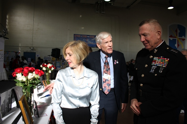 From left, Denise Peach of Arnold looks at a photo of the Honor Salute that was performed for her husband two weeks before he passed away. Hospice of the Chesapeake We Honor Veterans Committee member Bill Lovelace describes the salute to retired Marine Corps Lt. Gen. Steven A Hummer. (Elyzabeth Marcussen)