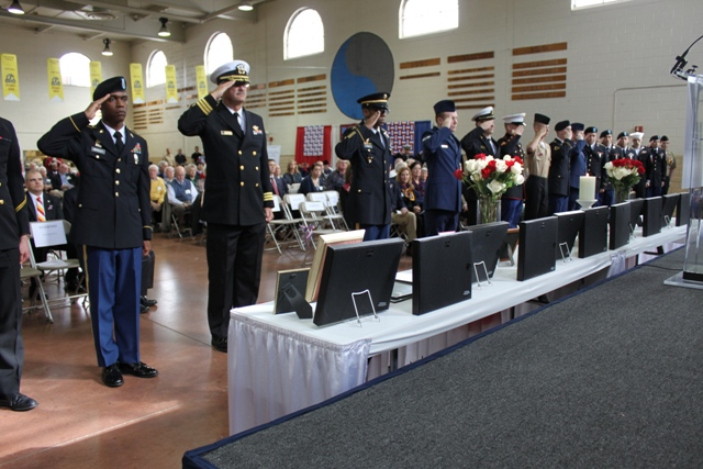 Fort Meade Garrison Command Sgt. Rodwell Forbes leads an Honor Salute performed by dozens of uniformed active duty military personnel, veterans, midshipmen and NJROTC students. (Elyzabeth Marcussen)