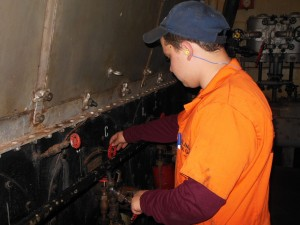 Evan Milbourne adjusts a valve on one of the Brown's two steam boilers. (Anthony C. Hayes)