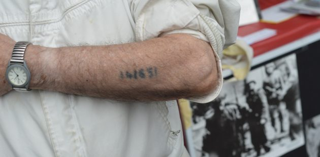 Holocaust survivor David Tuck shows the number tattooed on his arm by the Nazis (Anthony C. Hayes)