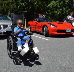 A wheelchair-bound child awaits his turn to sit in a Chevrolet Corvette. On Saturday, July 7, 2018, the Mason-Dixon Chapter of the National Corvette Restorers Society (NCRS) paid its annual visit to the Mt. Washington Pediatric Hospital in Baltimore (credit Anthony C. Hayes).