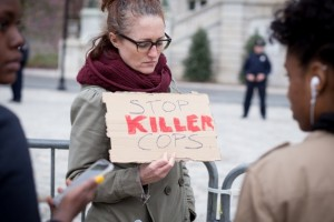 A woman in Baltimore protests against police brutality two days, before riots broke out in the city, stemming from the death of Freddie Gray. (Erik Hoffman)