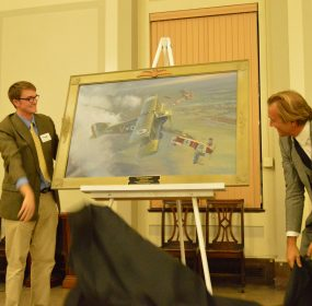 "Francis Warrington Gillet IV and his father, Francis Warrington Gillet III, remove the cover from the Michael O'Neal painting titled ""Maryland Over Flanders"". (Anthony C. Hayes)"