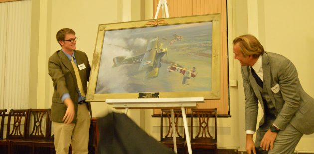 """Francis Warrington Gillet IV and his father, Francis Warrington Gillet III, remove the cover from the Michael O'Neal painting titled """"Maryland Over Flanders"""". (Anthony C. Hayes)"""