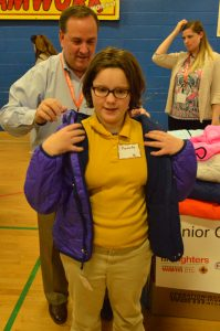 Operation Warm volunteer Mike Heiner of Horizon Services helps a student into her new winter coat. (Anthony C. Hayes)