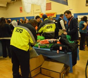 Baltimore City firefighters help distribute winter coats as part of Operation Warm. (Anthony C. Hayes)