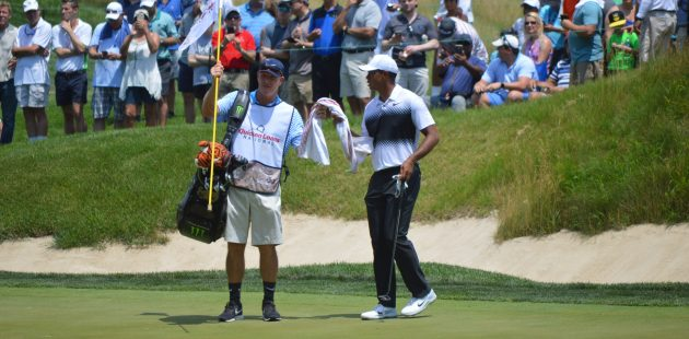Caddie Joe LaCava hands Tiger Wods a towel at the 2018 Quicken Loans National in Potomac, MD. (Anthony C. Hayes)