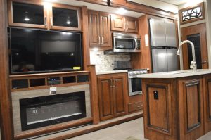 The interior of an RV at the 2018 Maryland RV Show. The well-appointed kitchen and den areas in a number of RVs included a TV, full-size refrigerator and gas fireplace. RVs such as this ranged in price from $150,000 - $200,000. (Anthony C. Hayes)