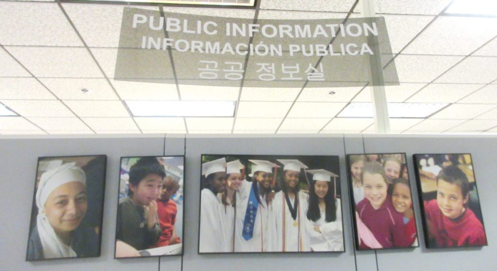 The sign in the public information office in the school system headquarters, in English, Spanish and Korean, typifies the diversity in local schools. Len Lazarick photo