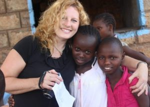 Tracie Jones in Africa with two smiling orphaned children.