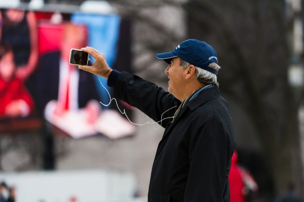 "Inauguration Day: ""The digital age"" A man uses his smart phone to live stream or video call from the National Mall moments after the Inauguration of President Trump. In the background President Trump signs his first executive order. (Michael Jordan)"