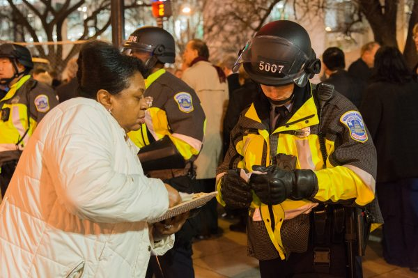 Inauguration Day: A police officer in riot formation and gear assists a party goer with directions. (Michael Jordan)