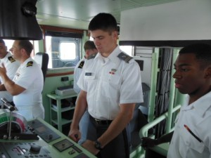 Army cadet Auten takes the helm under the watchful eye of Midshipman Jonathan X. Pullman. (Anthony C. Hayes)