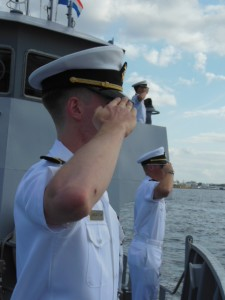 Midshipmen pause to salute the Star Spangled Banner. (Anthony C. Hayes)