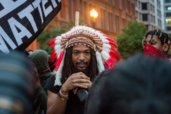 "Pierre Branson calls himself an ""Indigenous Aboriginal"" during a march at New York Ave NW and 15th St. NW (Mike Jordan/BPE)"