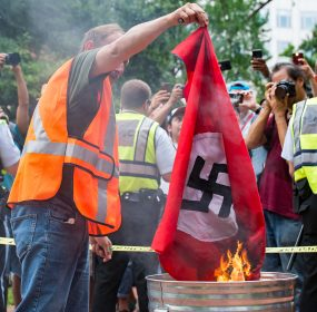 A flag with a confederate battle flag on one side and a swastika on the other is burned by anti-Unite the Right 2 protesters. (Mike Jordan/BPE)