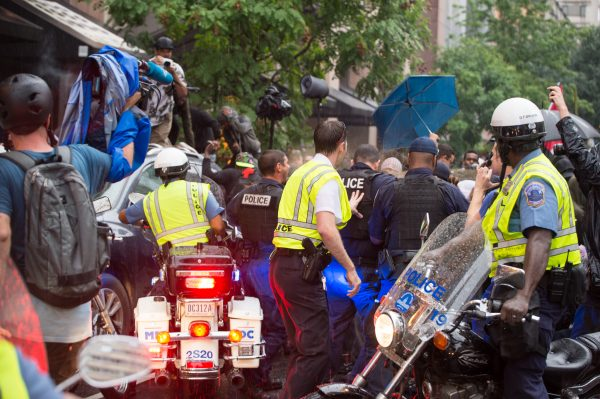 Police form a line to contain anti-Unite the Right 2 protesters. Anti Unite the Right 2 protesters are seen in a violent clash with police on G St NW. Protesters threw objects, launched flares, stood on cars and pulled up trash cans. Police deployed pepper spray. (Mike Jordan/BPE)