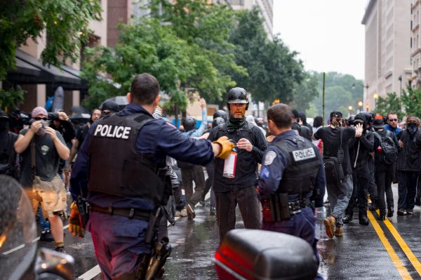 Washington, DC. Aug. 12, 2018: An anti-Unite the Right 2 protester gets pepper sprayed during a violent clash with police on G St NW. Protesters threw objects, launched flares, stood on cars and pulled up trash cans. Police deployed pepper spray. (Mike Jordan/BPE)