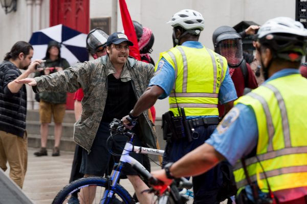 Washington, DC. Aug. 12, 2018: Anti-Unite the Right 2 protesters are seen confronting Washington DC police office moments before a violent clash with police erupted on G St NW. Protesters threw rocks and other objects, launched flares, stood on cars and pulled up trash cans. Police deployed pepper spray. (Mike Jordan/BPE)