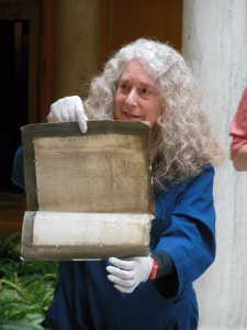 Terry Drayman-Weisser gently lifts a photograph of the Declaration of Independence. (Anthony C. Hayes)