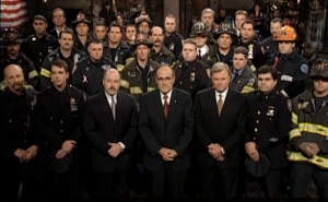 September 29, 2001- Mayor Giuliani stands onstage with members of the NYPD and NYFD (screenshot from NBC.com)